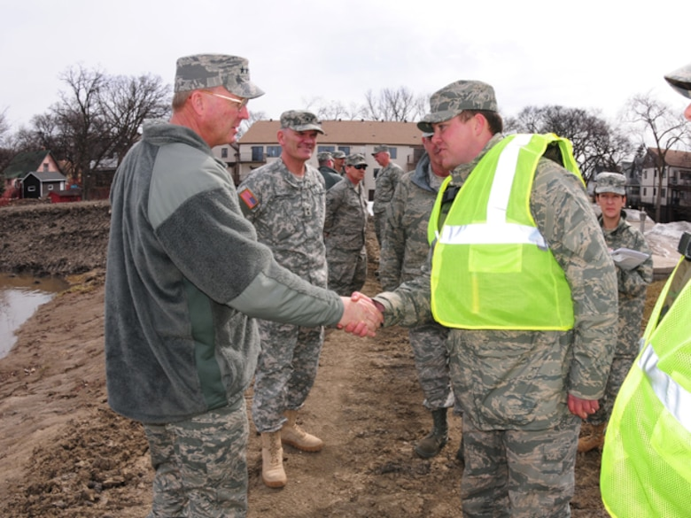 Gen. Craig R. McKinley, chief of the National Guard Bureau, shakes hands with Staff Sgt. Adam Kapaun, 119th Wing, while walking dike patrol near the Oak Grove Lutheran School on March 22.  McKinley spent the day in Fargo, N.D. visiting the Guardsmen currently on flood duty in the state.