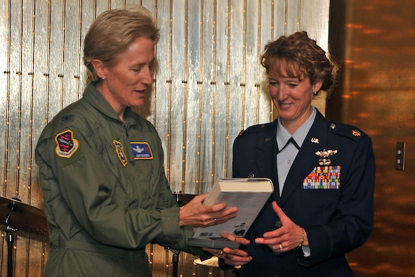 PETERSON AIR FORCE BASE, Colo. -- Col. Joan Sandene, 21st Space Wing senior individual mobilization augmentee, presents a book and 21st SW memento to Maj. Melissa May, U.S. Air Force Academy Cadet Squadron 21 Air Officer commanding, at the Women's History Month luncheon. Major May, a senior F-16 pilot who earned the Distinguished Flying Cross medal for a 2003 mission over Baghdad, was the guest speaker at the luncheon, held March 17 here at The Club. (U.S. Air Force photo/Dennis Howk)