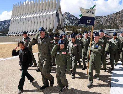 Lily Rackley, Cadet 1st Class Gary Whiteman and Cadet for a Day Kai Rackley salute during the noon meal formation at the Air Force Academy March 5, 2010. Other events during the Rackley family's visit included a tour of the Cadet Chapel and chemistry labs and a chance to try out flight simulators. Cadet Squadron 12 hosted the family for the two-day event. (U.S. Air Force photo/Rachel Boettcher)