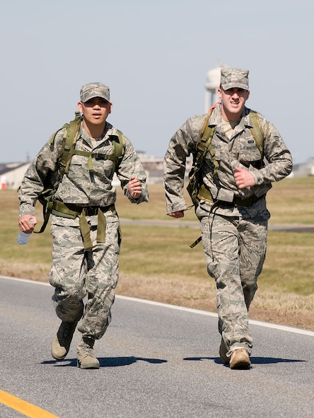Staff Sgt. Herbert Dungca (left) and Senior Airman Jonathan Howard, Air Force Mortuary Affairs Operations Center Dignified Transfer team members, pick up the pace during the 436th Security Forces Squadron's 11th Annual Ruck March held March 20. The annual 6.2 mile march is a fundraiser to honor the veterans of the Korean War who fought in the Battle of the Chosin Reservoir. (U.S. Air Force photo/Jason Minto)