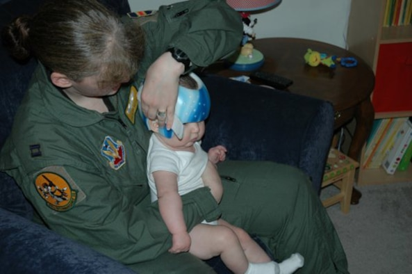 OFFUTT AIR FORCE BASE, Neb. -- Capt. Sonja Hosler, the mobility flight chief for the 45th Reconnaissance Squadron, holds her six-month-old son, Clark Alexander, while she carefully removes his cranial helmet. Clark required the helmet to correct a severe flat spot on his head, officially known as plagiocephaly Captain Hosler and her husband Adam were able to purchase the helmet after receiving a $2,500 grant from the Air Force Aid Society. U.S. Air Force Courtesy Photo