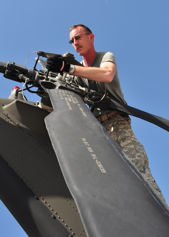 Specialist Ryan Boyer, aircrew member, 1st Battalion, 228th Aviation Regiment, realigns the rear rotor on a UH-60 Blackhawk March 21. The 1-228th deployed in support of Joint Task Force-Haiti from Soto Cano Air Base, Honduras March 21 brining more than 180,000 pounds of equipment, UH-60s and personnel. (U.S. Air Force photo/Staff Sgt. Bryan Franks)