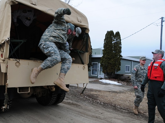 Sgt. Brian Steckler, of the 815th Engineer Company, jumps out of the back of a quick response force (QRF) truck March 22, as his QRF team responds to a request for assistance from the Cass County Sherriff's Dept.  The QRF team is assisting an elderly rural resident to temporarily vacate her home because the rising flood water has left it inaccessible to automobile traffic.