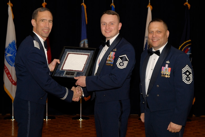 VANDENBERG AIR FORCE BASE, Calif. -- Master Sgt. Christopher Hart, from the 460th Space Communications Squadron at Buckley Air Force Base, Colo., receives the 14th Air Force Senior NCO of the Year Annual Award from Lt. Gen. Larry James, the 14th Air Force commander, and Chief Master Sgt. James MacKinley, the 14th AF command chief master sergeant, during the 14th Air Force Annual Awards Ceremony at the Pacific Coast Club here Thursday, March 18, 2010.   (U.S. Air Force photo/Senior Airman Andrew Satran)
