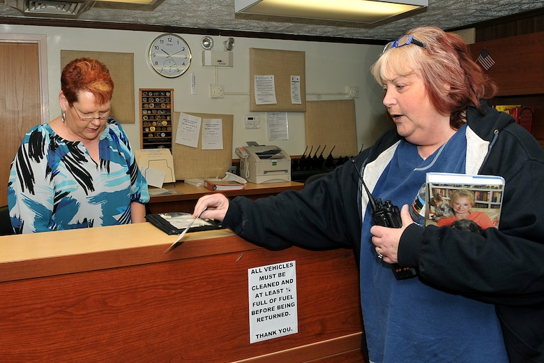 OFFUTT AIR FORCE BASE, Neb. - (From left) Dispatcher Betty McCubbin gives keys to base shuttle driver Sheila Wilen-Paulus before shift change inside the vehicle operations office March 19. Both Ms. McCubbin and Ms. Wilen-Paulus are part of the 55th Mission Support Group's Logistics Support Division. The division's vehicle operations section takes care of Offutt's transportation needs using a fleet of more than 60 vehicles.    U.S. Air Force photo by Charles Haymond