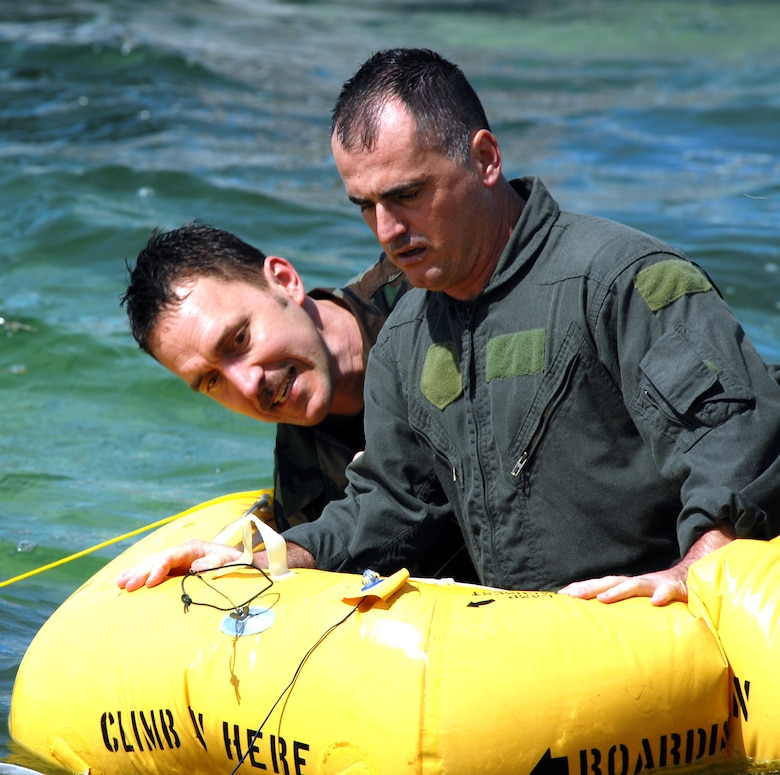 Master Sgt. Cary Garland, flight attendant, and Master Sgt. Joe Smiley, crew chief,  201st Airlift Squadron, evaluate the repair of a puncture hole in their raft during their water survival training at Naval Air Station Key West, Fla. Mar. 15. (U.S. Air Force photo by Tech Sgt. Tyrell Heaton/Released)