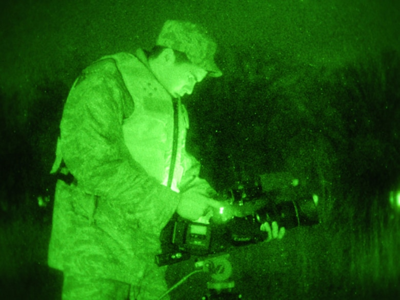 Senior Airman Nathanael Baardson, of the 119th Wing, uses a night-vision lens to videotape a pair of North Dakota National Guard quick response force (QRF) team members March 24 as they monitor floodwater along levees in Harwood, N.D. Baardson is a member of the N.D. National Guard public affairs team documenting the activities of the military flood mission for historical, internal Department of Defense briefings and civilian media relations purposes. (DoD photo by Senior Master Sgt. David H. Lipp) (Released)