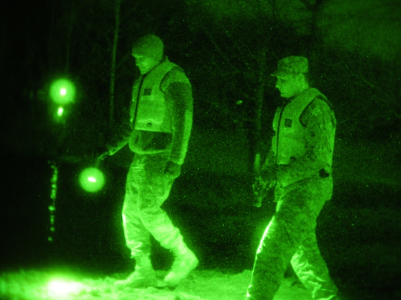 Senior Airman Anthony Rezac, of the 119th Civil Engineer Squadron, (left) and Spc. Nick Strom, of the 815th Engineer Company (Wishek, N.D.), walk along an earthen levee using flashlights during the evening hours of March 24 in Harwood, N.D. The pair of North Dakota National Guard members are part of a quick reaction force (QRF) team staging out of the Harwood Community Center who take a turn monitoring the floodwater as residents sleep. The residents of Harwood are able to monitor the levees themselves during the daylight hours. The nighttime levee walking is one the remaining tasks for the QRF teams as much of the floodwater in the area begins to recede. (DoD photo by Senior Master Sgt. David H. Lipp) (Released)