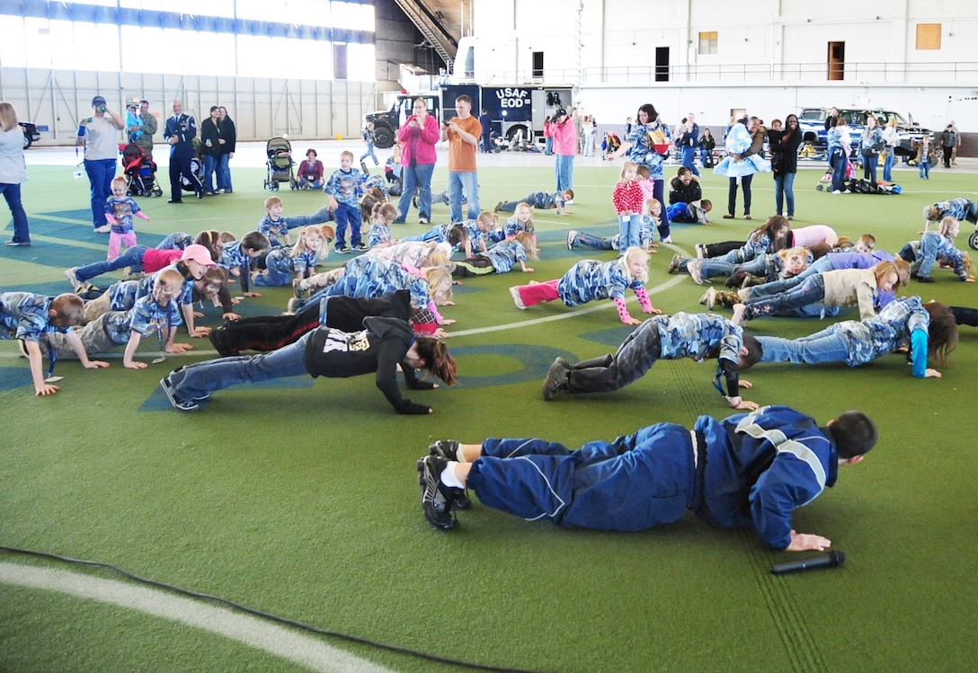 Children of base Airmen do push-ups for a physical training demonstration during Kids, Spouses and Teachers Understanding Deployment Operations event March 13, 2010, at Ellsworth Air Force Base, S.D. Senior Airman Zachary Christy, 28th Force Support Squadron food services specialist, teaches the children how to do a proper push-up. (U.S. Air Force photo/Airman 1st Class Anthony Sanchelli)