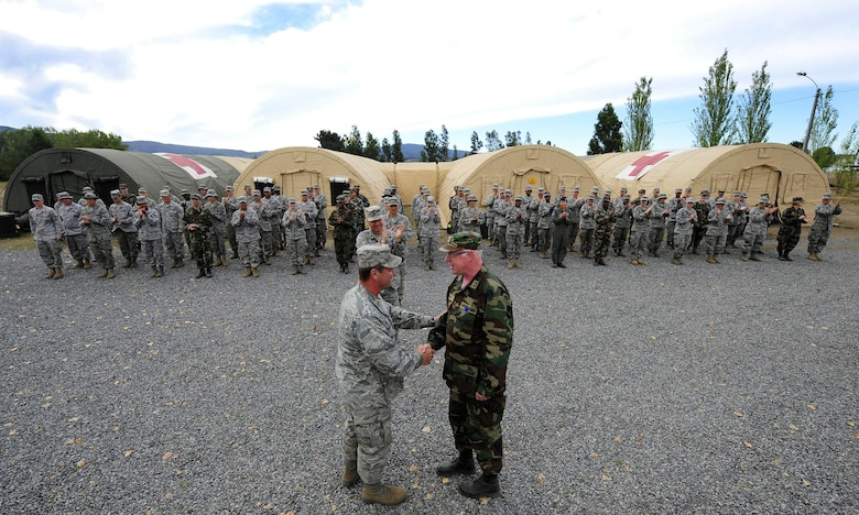 Col. David Garrison and Chilean army Lt. Col. (Dr.) Guillermo Uslar shake hands during the final hand-off of the expeditionary hospital March 26, 2010, in Angol, Chile. Members of the Air Force Expeditionary Medical Support team completed a humanitarian mission to build a hospital and augment medical care for members of the Angol community. A team of Airmen built, staffed and equipped a field hospital to serve more than 110,000 people in the Angol region. During a ceremony March 24, U.S. government officials donated the hospital to the local Chilean medical community. (U.S. Air Force photo/Senior Airman Tiffany Trojca)