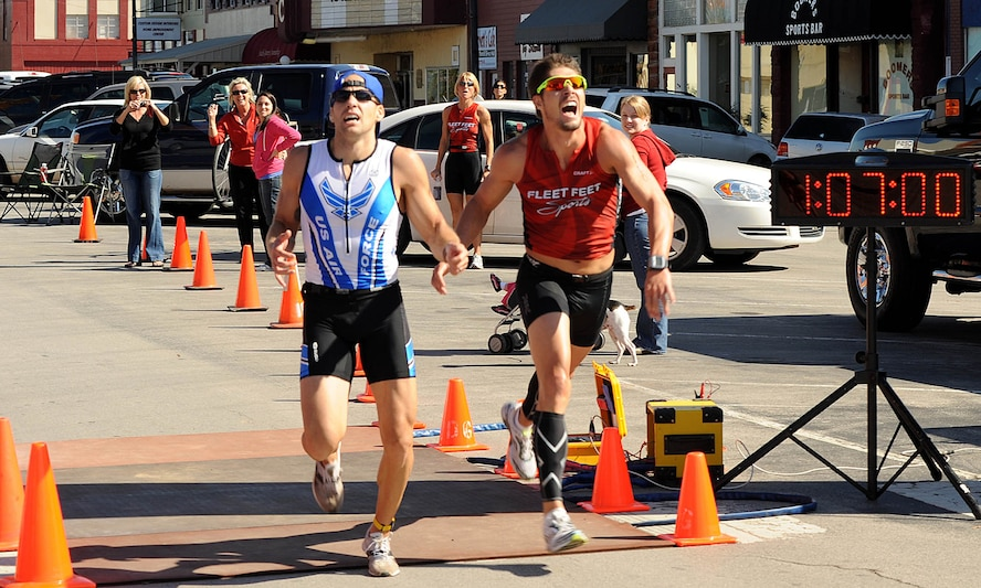 John Dalrymple, left, crosses the finish line at the Fall Classic Duathlon in Purcell just half a second before the second-place finisher. The air battle manager with the 963rd Airborne Air Control Squadron is currently training to compete in the Route 66 Triathlon in El Reno in June. (Courtesy photo)