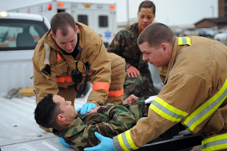 WHITEMAN AIR FORCE BASE, Mo., -- Senior Airman Kasey Krautkreme (left) and Airman 1st Class Timothy Vanden Haak (right) 509th Civil Engineer Squadron fire fighters, prepare to lift Airman 1st Class Jacob Davis, 394th Combat Training Squadron, onto a stretcher to carry him over for treatment of his simulated gunshot wound, during the active shooter exercise here March 24, 2010. The 509th Security Forces Squadron, and many others throughout the Air Force are training to deal with these types of threats from within. Hoping to reduce the number of casualties if such situations occur, a quick and effective response was the goal of the training exercise. (U.S. Air Force photo/Staff Sgt. Jason Huddleston)  (Released)