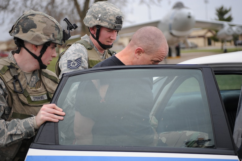 WHITEMAN AIR FORCE BASE, Mo., -- Senior Airman Anthony Dykhuis and Tech. Sgt. Jonathon Huber, 509th Security Forces Squadron, put Lt. Col. Daniel Semsel, 509th Mission Support Squadron deputy commander, into the back of the squad car after being apprehended during the active shooter exercise here March 24, 2010. The 509th SFS, and many others throughout the Air Force are training to deal with these types of threats from within. Hoping to reduce the number of casualties if such situations occur, a quick and effective response was the goal of the training exercise. (U.S. Air Force photo/Staff Sgt. Jason Huddleston)  (Released)