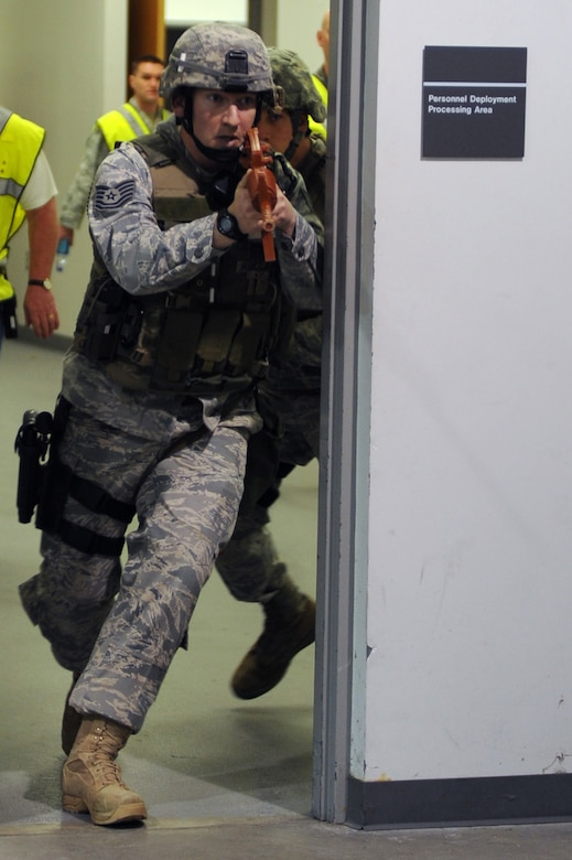 WHITEMAN AIR FORCE BASE, Mo., -- Tech. Sgt. Jonathon Huber and Tech. Sgt. Bryan Gilbert, 509th Security Forces Squadron, charge through a door searching for the person who was attacking the base, during the active shooter exercise here March 24, 2010. The 509th Security Forces Squadron, and many others throughout the Air Force are training to deal with these types of threats from within. Hoping to reduce the number of casualties if such situations occur, a quick and effective response was the goal of the training exercise. (U.S. Air Force photo/Staff Sgt. Jason Huddleston)  (Released)