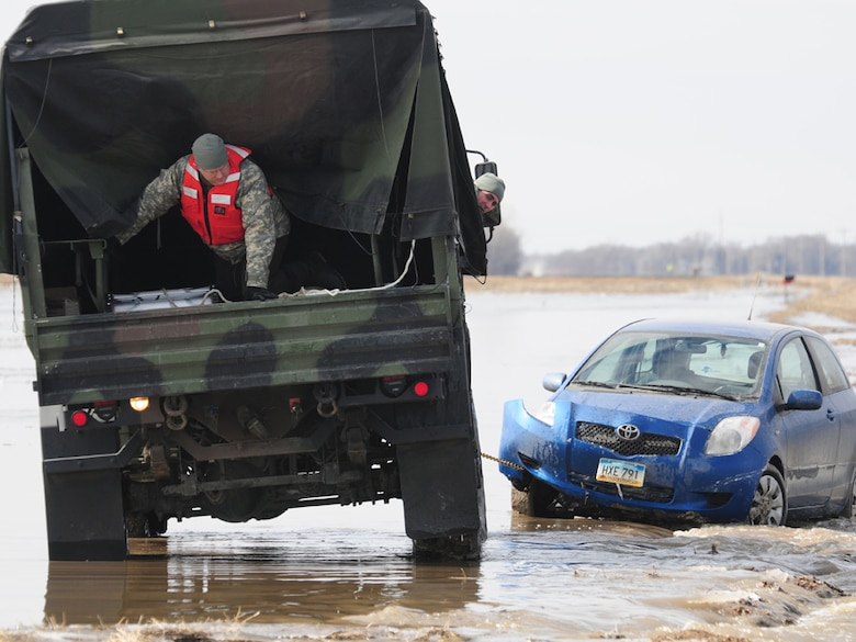 Spc. Jeremy Kasperson sits in the rear of a North Dakota National Guard truck as he gives directions for backing out of a washed out road March 25 in rural Cass County. The truck is towing a stranded automobile from the washed out roadway. Cass County Tactical Operations Center liaison officer Capt. Grant Larson, of the 119th Maintenance Squadron, North Dakota Air National Guard, can be seen giving guidance from the cab of the truck. Kasperson is a member of the 815th Engineer Company's North Dakota National Guard quick response force (QRF) team that is being called to the scene by the Cass County Sherriff's Department to assist with the vehicle recovery. The driver of the vehicle was able to get clear of the car and make his way through the freezing water to safety before help arrived. (DoD photo by Senior Master Sgt. David H. Lipp) (Released)