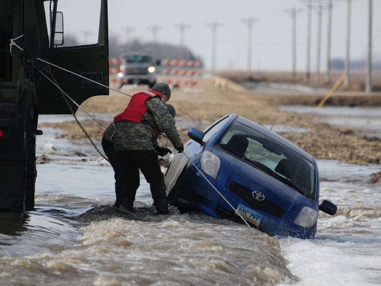 Sgt. Preston Steele and Spc. Jeremy Kasperson, both of the 815th Engineer Company, attach a towing chain to a partially submerged vehicle March 25 on a washed out portion of a gravel road a few miles west of Harwood, N.D.  Steele and Kasperson are members of a North Dakota National Guard quick response force (QRF) team that is being called to the scene by the Cass County Sherriff's Department to assist with the vehicle recovery.  The driver of the vehicle was able to get clear of the car and make his way through the freezing water to safety before help arrived.  (DoD photo by Senior Master Sgt. David H. Lipp) (Released)