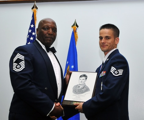 ANDERSEN AIR FORCE BASE, Guam - Staff Sgt. Peter Pleasanton, 36th Munitions Squadron, is presented with the Levitow Award during the Airman Leadership graduation ceremony here March 25. The Levitow Award is presented to the Airman Leadership School graduate who excels in all aspects of the course including leadership, public speaking, academics, and drill. The award is named after John Levitow who received the Medal of Honor in 1970. (U.S. Air Force photo by Airman 1st Class Julian North)