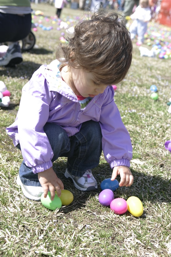 A young girl reaches down to pick up eggs at the 2010 Eggstravaganza egg hunt.  Along with the egg hunt, families in attendance also got to enjoy a number of arts, crafts and a free hotdog lunch.