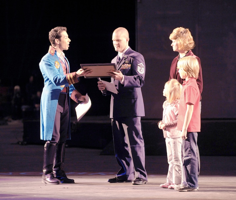 "Master Sgt. Cameron Rogers, along with his wife Maggie and children Sam and Laine, receive a certificate from Magical Zingmaster Alex Ramon designating the Rogers family as guest ringmasters for the Ringling Bros. and Barnum & Bailey ""Zing Zang Zoom"" circus performance March 26, 2010, at George Mason University's Patriot Center in Fairfax, Va.  Sergeant Rogers is the Air Force District of Washington's UH-1N helicopter program manager at Bolling Air Force Base, D,C, The Rogers family was invited to serve as guest circus ringmasters representing military families worldwide in observance of Year of the Air Force Family. (U.S. Air Force photo/Jim Varhegyi)"