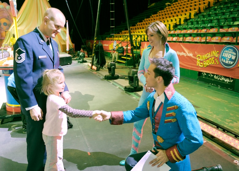 "Master Sgt. Cameron Rogers looks on as his 5-year-old daughter Laine shakes hands with Magical Zingmaster Alex Ramon prior to the start of the Ringling Bros. and Barnum & Bailey ""Zing Zang Zoom"" circus performance March 26, 2010, at George Mason University's Patriot Center in Fairfax, Va.  Looking on is the circus' human cannonball and former Air Force reservist Tina Miser. Sergeant Rogers is the Air Force District of Washington's UH-1N helicopter program manager at Bolling Air Force Base, D.C. The Rogers family was asked to serve as guest circus ringmasters representing military families worldwide in observance of Year of the Air Force Family. (U.S. Air Force photo/Jim Varhegyi)"