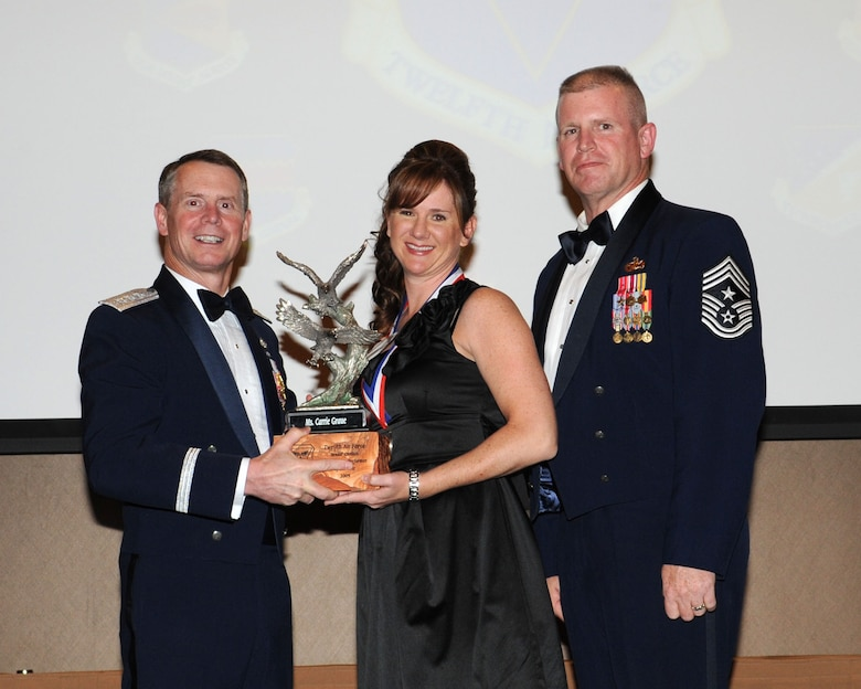 DAVIS-MONTHAN AIR FORCE BASE, Ariz. -- Lt. Gen. Glenn Spears (left), 12th Air Force (Air Forces Southern) commander, and Chief Master Sgt. Harold Clark (right), 12th AF (AFSOUTH) command chief, present the Outstanding Performer of the Year award to Ms. Carrie Graue Mar. 9. Ms. Graue is from Headquarters 12th AF, Davis-Monthan Air Force Base, Ariz.  (U.S. Air Force Photo by Airman Jerilyn Quintanilla)