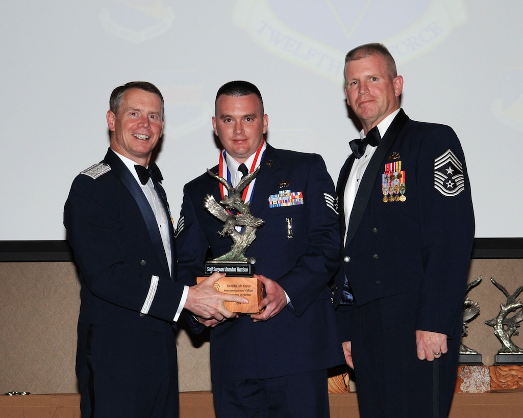 DAVIS-MONTHAN AIR FORCE BASE, Ariz. -- Lt. Gen. Glenn Spears (left), 12th Air Force (Air Forces Southern) commander, and Chief Master Sgt. Harold Clark (right), 12th AF (AFSOUTH) command chief, present the Outstanding Performer of the Year award to Staff Sgt. Brandon Harrison Mar. 9. Sergeant Harrison is from the 432nd Wing, Creech Air Force Base, Nev. (U.S. Air Force Photo by Airman Jerilyn Quintanilla)