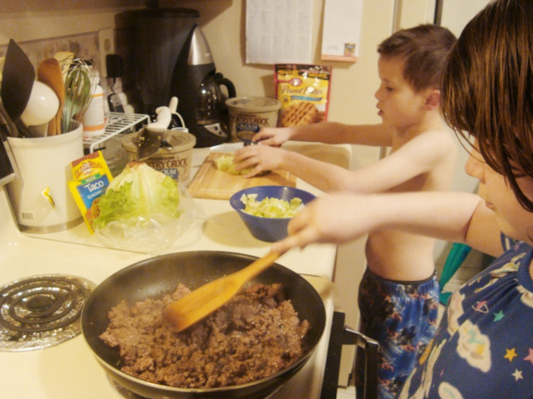 """Kristina Urban, 10, cooks the beef while her brother, Paul, 6, shreds lettuce for dinner, March 17, 2010, at at Joint Base Langley-Eustis, Va. Once a week, Kristina and Paul are allowed to prepare a meal for """"family cook night"""" under their parents' supervision. Families learn to make nutritious food choices with FitFamily. Kristina and Paul are the children of Carol and Tech. Sgt. Lou Urban. Sergeant Urban is currently deployed from the 1st Equipment Maintenance Squadron. (U.S. Air Force photo)"""