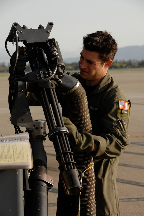 Staff Sgt. Sean Pellaton, an HH-60G Pave Hawk aerial gunner from the 129th Rescue Squadron, conducts a pre-flight inspection on a GAU-2C Mini-gun at Moffett Federal Airfield, Calif., March 24, 2010. (Air National Guard photo by Tech. Sgt. Ray Aquino)