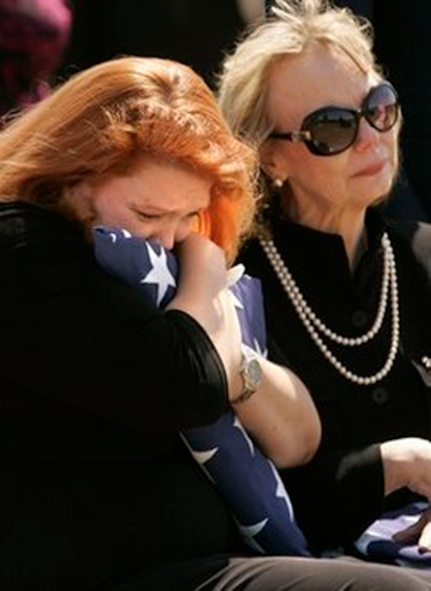 Christy Hollerich, left, holds a flag as her mother Susan Miller looks on at the funeral of Air Force Maj. Curtis Daniel Miller on Monday, March 29 in Dallas. Maj. Miller, of Palacios, Texas, was buried Monday afternoon at Dallas-Fort Worth National Cemetery, with full military honors. His funeral comes 38 years to the day after his gunship was shot out of the sky over Laos during the Vietnam War. His remains were processed at the Air Force Mortuary Affairs Operations Center at Dover Air Force Base, Del. (AP Photo/Mike Fuentes)