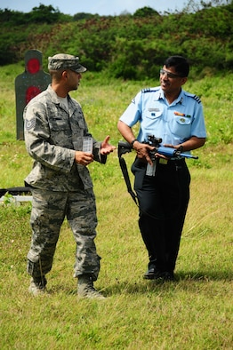 ANDERSEN AIR FORCE BASE, Guam ? Tech. Sgt. Marcus Serrano from the 736th Security Forces discusses small arms firing technique with a visitor from India as part of the Subject Matter Expert Exercise, here on March 24. Papa New Guinea, Mongolia, India, and the Philippines were among the nations represented to exchange ideas on security matters pertaining to air base defense. (U.S. Air Force photo by A1C Jeffrey Schultze)