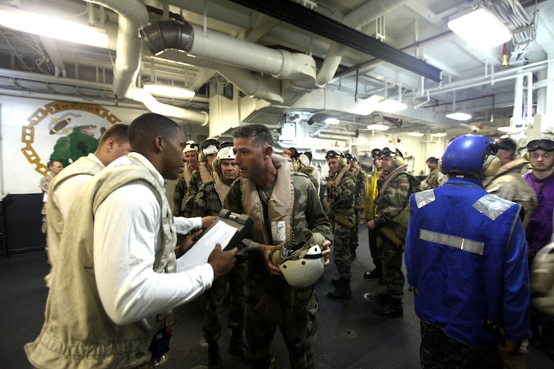 Marine LCpl. Antoine Sanders verifies a roster with LtCol. Valery Putz of the French Foreign Legion as a team from the French Foreign Legion's 13th Demi-Brigade arrive on USS Nassau, March 31, 2010.  The team of French soldiers traveled from the east-African country of Djibouti to meet with commanding officers of the 24th Marine Expeditionary Unit, Amphibious Squadron 8, and USS Nassau as part of a key leader engagement between the two countrie's services in an effort to reinforce military ties and familiarize the French troops with the unique relationship of the Marine-Navy team.