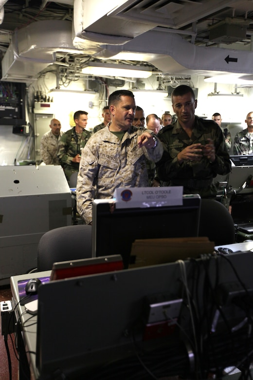 Col. Pete Petronzio, commanding officer, 24th Marine Expeditionary Unit, explains the functions of the Marine operations center aboard USS Nassau to Col. Thierry Burkard, commanding officer of the French Foreign Legion's 13th Demi-Brigade March, 31, 2010.  The 24th MEU hosted a visit with a team of French soldiers from the 13th Demi-Brigade as a key leader engagement between the U.S. and French units in an effort to reinforce military ties and familiarize the French with the unique, Marine-Navy team that comprises a Marine Expeditionary Unit.