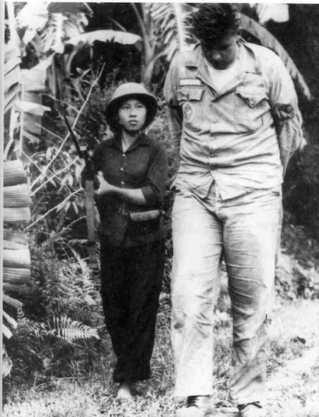 POW Airman First Class Bill Robinson is guarded by a North Vietnamese soldier after his capture on September 20, 1965.  (USAF Photo)
