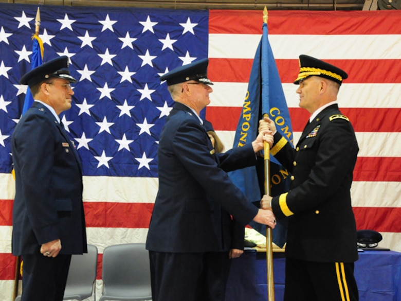 "Maj. Gen. David Sprynczynatyk, the North Dakota adjutant general, right, accepts a symbolic command flag from Brig. Gen. Alan Palmer, the North Dakota National Guard Air Component Commander, and prepares to hand off the flag to newly promoted Brig. Gen. Cecil ""Bud"" Hensel, far left, symbolizing the assumption of command during the change of command ceremony May 1, at the North Dakota Air National Guard, Fargo, N.D."