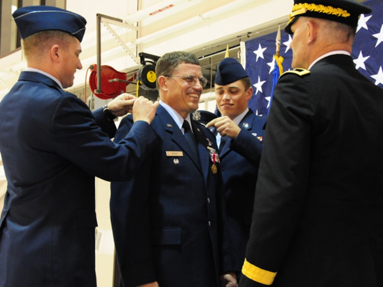 "Col. Cecil  ""Bud"" Hensel Jr. pins on the rank of Brig. Gen. with the help of his sons Capt. Jonathon Hensel, left and Staff Sgt. Brian Hensel, as Maj. Gen. David Sprynczynatyk, the North Dakota adjutant general looks on, May 1, at the North Dakota Air National Guard, Fargo, N.D."