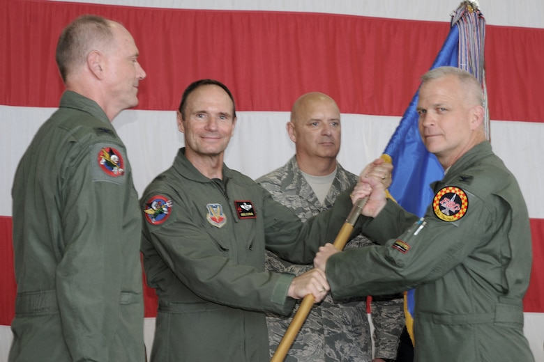 """Colonel William Drew """"Toto"""" DeHaes accepts the 132nd Fighter Wing guidon from Brig. Gen. Gregory Schwab, Assistant Adjutant General, Air Component, Iowa National Guard assuming command of the Wing during a Change of Command ceremony held in the west hanger at the Des Moines ANGB. Saturdays ceremony was the twelfth in the units almost 70 year history. (from left to right, Col. Mark """"Eddie"""" Hammond, Brig. Gen. Gregory """"Koa"""" Schwab, Chief Master Sgt. Lowell Schellhase Jr., Col. William Drew """"Toto"""" DeHaes)(U.S. Air Force photo Senior Master Sgt. Tim Day)(""""Released"""")"""