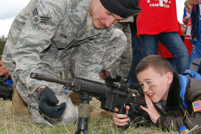 Senior Airman Jacob Heine familiarizes Andy Miller with an M-4 rifle during Operation Junior Deployer at the Air Force Academy May 1, 2010. Airman Heine is a patroller with the Academy's 10th Security Forces Squadron. (U.S. Air Force photo/Staff Sgt. Don Branum)