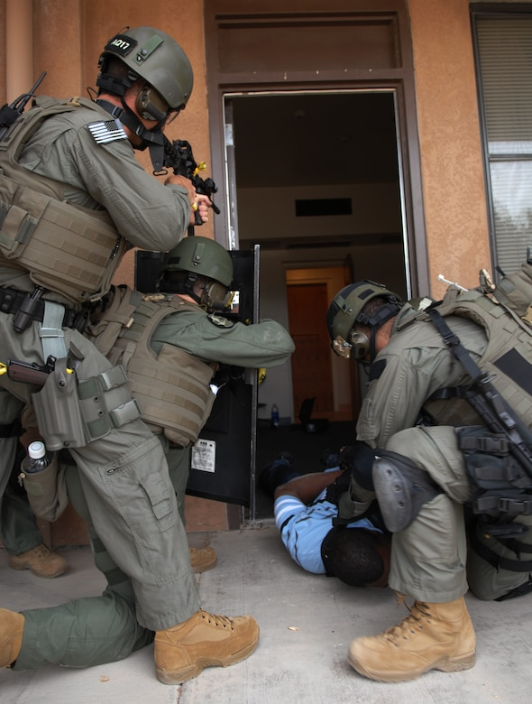 HOLLOMAN AIR FORCE BASE, N.M. -- A member of the Albuquerque Federal Bureau of Investigation restrain the alleged perpetrator during a hostage exercise while his partners cover him April 28, 2010, at the base dormitories. The exercise involved 49th SFS Quick Reaction Force members, 49th SFS hostage negotiators; FBI hostage negotiators and FBI Special Weapons and Tactics teams from El Paso, Texas; Las Cruces and Albuquerque, N.M. Within the past year, Holloman security forces and the FBI have begun exercising joint Crisis Negotiation Team training.  This was the first exercise of its kind at Holloman involving both Crisis Negotiation and the SWAT teams. Future exercises are planned and will be larger in scope. (U.S. Air Force photo by Airman 1st Class Joshua Turner / Released)