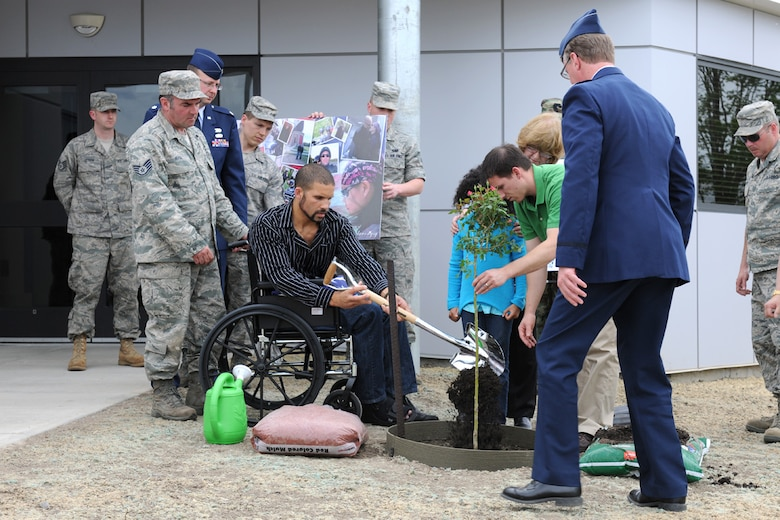 US Air Force Staff Sgt. Preston J. Cox shovels dirt on a rose tree being planted outside of the communications building at Hancock Field in Syracuse, NY on 2 May 2010. The tree was being planted as a memorial for Cox's fiancee, US Air Force Staff Sgt. Linda Monelavongsy, who was a member of the 174th Fighter Wing Communications Flight.  Monelavongsy passed away in a motorcycle accident on 21 April 2010. (US Air Force photo by Staff Sgt. James Faso/Released)