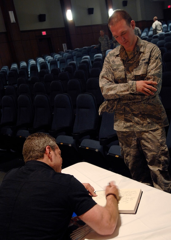 Senior Airman Richard Gilbert III waits as comedian Bernie McGrenahan signs his book following his comedy routine April 30, 2010, on Joint Base Charleston, S.C. Bernie McGrenahan tours around the United States speaking to America's youth about substance abuse, sexual assault and high-risk decisions with a 30-minute stand-up routine and 30-minute inspirational message. Airman Gilbert is a loadmaster with the 701st Airlift Squadron. (U.S. Air Force photo/Senior Airman Timothy Taylor)