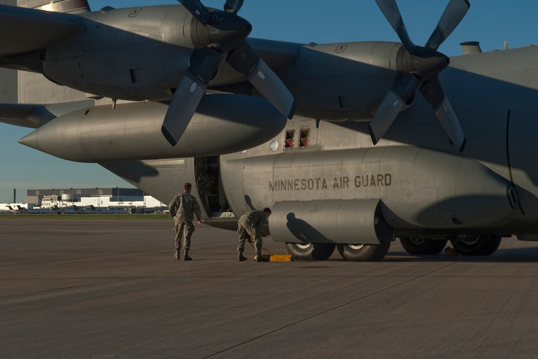 """Crew chiefs pull the chocks from under the wheels of a C-130 """"Hercules"""" cargo aircraft on May 1, 2010 as they prepare to launch on a deployment to Southwest Asia.  Minnesota Airmen from the St. Paul Air National Guard base will be transporting troops and supplies supporting Operation Enduring Freedom. USAF photo by Senior Master Sgt. Mark Moss (Released)"""