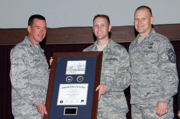 Technical Sgt. Brannen Parrish (center), Air University Public Affairs specialist, receives his Community College of the Air Force degree from Col. Charles W. Johnson (left), Barnes Center commander, and Chief Master Sgt. of the Air Force James A. Roy. Sergeant Parrish received the 350,000th CCAF degree. (Air Force photo/Melanie Rodgers Cox)