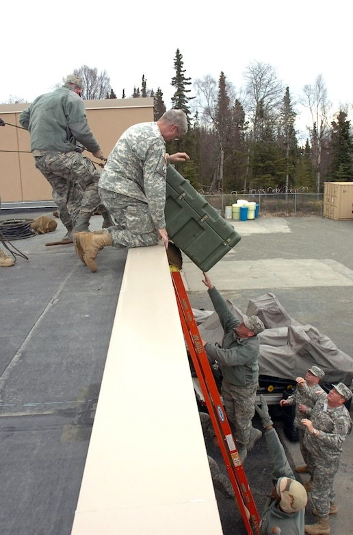 North Carolina Guardsmen lift a container onto the roof of the Alaska National Guard armory in Kenai during the Alaska National Guard Vigilant Guard 2010 exercise April 25. Vigilant Guard is an exercise program sponsored by the National Guard Bureau that allows Joint Forces Headquarters, Joint Task Forces and various field units to improve command and control and to exercise operational relationships with local, state, regional and federal partners. These Guardsmen are part of Joint Task Force Tarheel composed of service members from the Joint Forces Headquarter-North Carolina, 263rd Combat Communications Squadron, and 60th Troop Command an subordinate units.. (NCNG Photo by Sgt. Zach Otto; Joint Task Force – Tarheel, North Carolina National Guard)