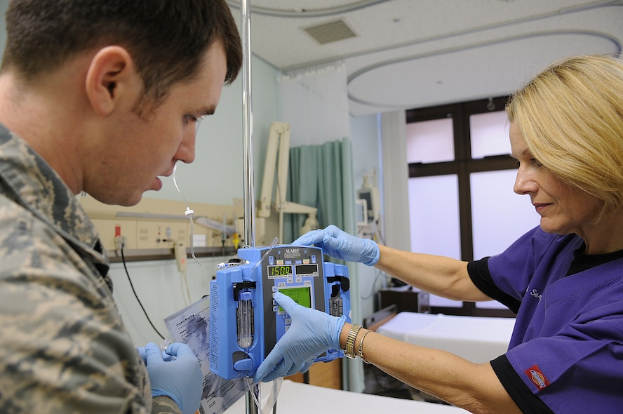 35th Surgical Operations Squadron Airmen, Maj. Carol Marta, infection control officer and clinical nurse, and Senior Airman Andrew Schaub, medical technician, prepares an intravenous machine for patient admission, May 11 at the 35th Medical Group hospital.  In honor of Nurses' Appreciation Week, nationally celebrated May 6 to 12, the 35th Medical Group honors nurses and medical technicians who serve the Misawa Air Base community. (U.S. Air Force photo/Senior Airman Jessica Lockoski)