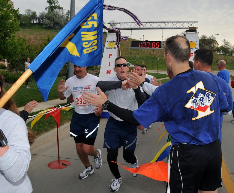 OFFUTT AIR FORCE BASE, Neb. -- Members of the 55th Mission Support Group are greeted by several high fives as they finish the third annual Bellevue-Offutt Runway Run May 9. More than 140 runners participated in the seven mile race which included about two miles on Offutt's runway. U.S. Air Force Photo by Jeff W. Gates