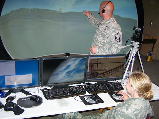 """Senior Master Sergeant Alan Van Pate (standing) calls in an airstrike to """"destroy"""" an enemy tank during joint combat air support training on the Joint Terminal Attack Controller (JTAC) virtual training dome at the Grayling Air Gunnery Range in Alpena, Mich. Technical Sergeant Claire LaFleur (seated) enters information into the simulator so that the simulated aircraft reacts as intended. The 711th Human Performance Wing, Human Effectiveness Directorate's Warfighter Readiness Research Division in Mesa, Ariz. is using the Grayling Range as a testing site for ways to improve JTAC training."""