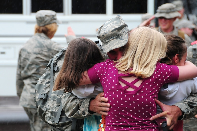 U.S. Air Force Senior Master Sgt. James Picconatto, 148th Fighter Wing Security Forces, embraces his three daughters as he arrives home at the Duluth, Minn., based Air National Guard base May 13, 2010. Approximately 35 Air National Guard members of the 148th Fighter Wing Security Forces Squadron returned to Duluth, Minn., after a 6-month deployment in southwest Asia. (U.S. Air Force photo by Master Sgt. Jason W. Rolfe/Released)