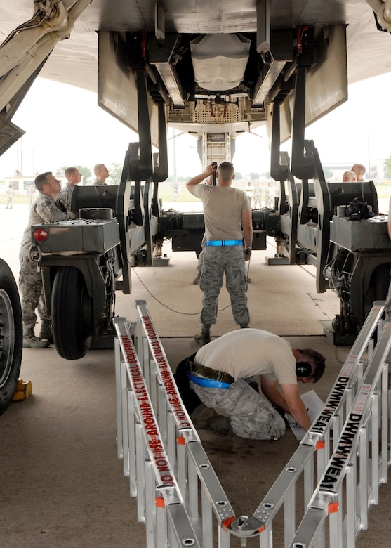DYESS AIR FORCE BASE, Texas - 7th Aircraft Maintenance Squadron Airmen check clearances May 12 here they load missiles while Global Strike Challenge inspectors observe. The 7th Bomb Wing is one of seven bomb wings to participate in Air Force Global Strike Command's first load competition. The competition consists of a uniform inspection, general knowledge test, tool inspection, munitions build, weapons load and B-1 Bomber pre-flight inspection. (U.S. Air Force photo/ Airman 1st Class Chelsea Browning)