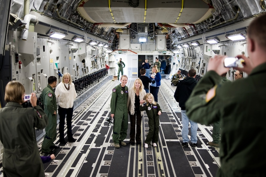 Pilot for a Day candidate Kaylie Bergen, age 6, and her mother Christy pause for a photo with 1st Lt. Eleanor Morgan, 4th Airlift Squadron, while touring a C-17 Globemaster III May 11 as part of McChord Field's Pilot for a Day program. (U.S. Air Force Photo by Abner Guzman)