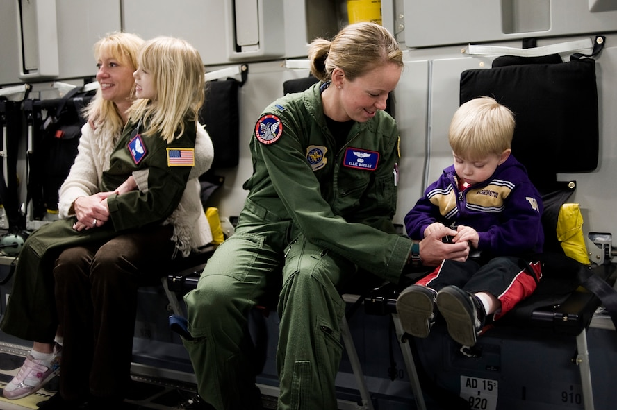 1st Lt. Ellie Morgan, 4th Airlift Squadron, center, assists Kaylie Bergen, 6, and brother Dylan, 3, with seatbelts in preparation for a photo-op onboard a C-17 Globemaster III May 11. (U.S. Air Force Photo by Abner Guzman)